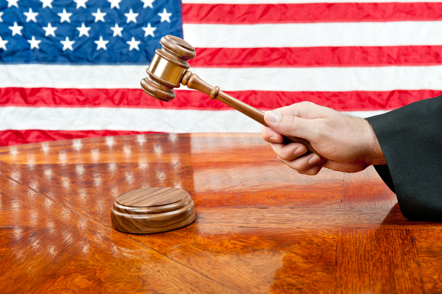 A judge's gown and gavel with sound block on deep, rich colored wooden desktop and American flag