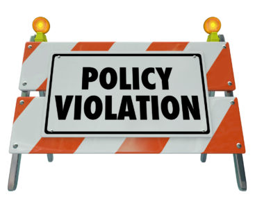 Policy Violation words on a road construction barrier or sign warning you of a rule or regulation that has been broken or violated