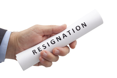 rolled letter of resignation in hand